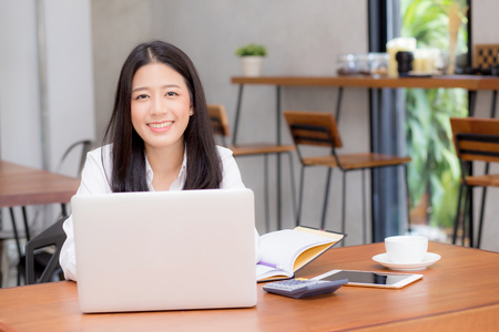 Beautiful asian young woman working online on laptop sitting at coffee shop, professional female freelancer using notebook computer with connect to internet for distance job. Banco de Imagens