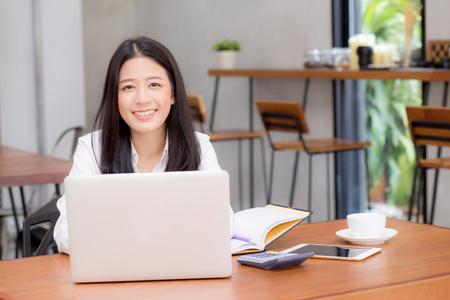 Mooie Aziatische jonge vrouw die online op laptopzitting bij koffiewinkel werken, professionele vrouwelijke freelancer die notitieboekjecomputer met verbinden met Internet voor afstandsbaan met behulp van.