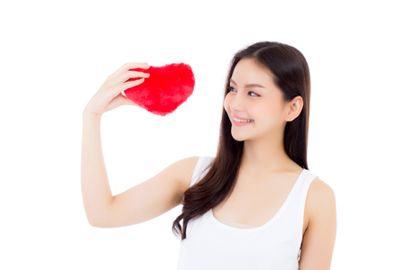 Portrait of beautiful asian young woman holding red heart shape pillow and smile isolated on white background, valentines day, holiday concept. Stock Photo