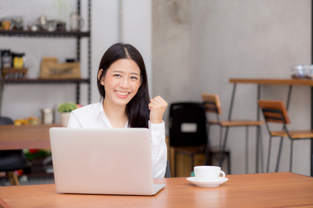 Beautiful asian young businesswoman excited and glad of success with laptop, girl using working computer coffee shop on desk, career freelance business concept.
