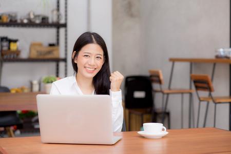 Schöne asiatische junge Geschäftsfrau aufgeregt und froh über Erfolg mit Laptop, Mädchen, das Arbeitscomputerkaffeestube auf Schreibtisch, freiberufliches Geschäftskonzept der Karriere verwendet.