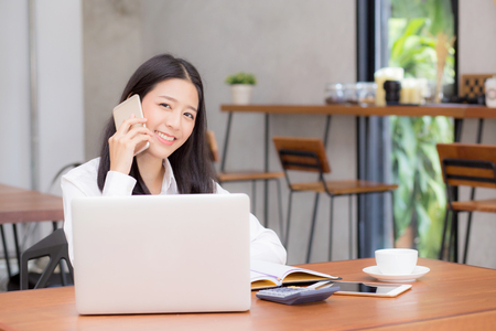 Beautiful asian young businesswoman excited and glad of success with laptop, girl taking mobile phone and working coffee shop on cement background, career freelance business concept.