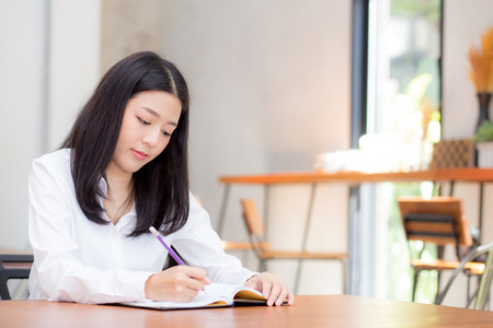 Beautiful business asian young woman writing on notebook on table, girl work at coffee shop, freelance business concept. 写真素材