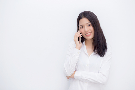 Beautiful young asian woman talking mobile phone and smile standing on cement background, freelancer female calling telephone, communication concept.