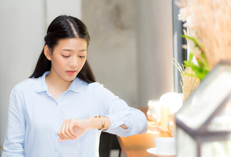 Beautiful asian young woman look at watch waiting for friend or someone, girl checking clock with appointment at coffee shop.