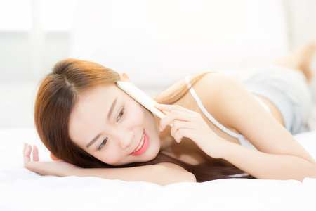Beautiful young asian woman smiling lying and relax on the bed in the morning, girl using mobile smart phone talking enjoy, communication concept.