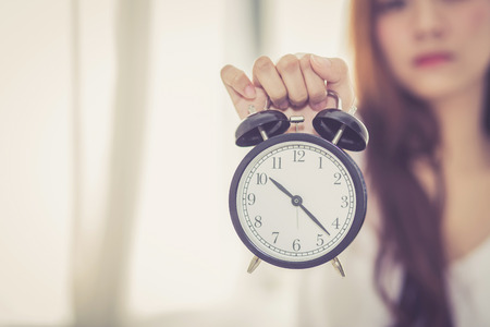 Beautiful asian young woman wake up in morning annoyed alarm clock holding hand, girl hurry wake late with appointment, lifestyle concept. Stock Photo