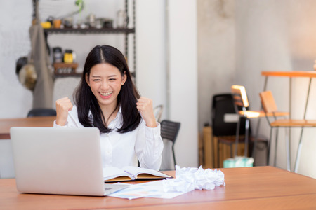 Beautiful asian young woman working online on laptop sitting at coffee shop, professional female freelancer with paper crumpled and using notebook computer with connect to internet for distance job.