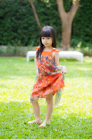 Beautiful portrait little girl asian of a smiling standing on green grass at the park, kid leisure and joyful in outdoor.