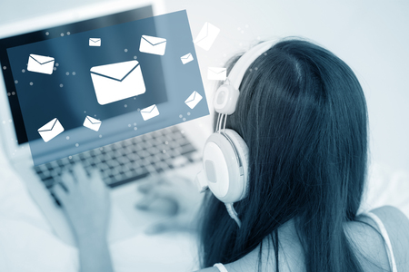 Beautiful asian young woman using a laptop computer keyboard with head phone of sending email for contact on network internet in blue tone, girl using notebook, communication concept. Archivio Fotografico
