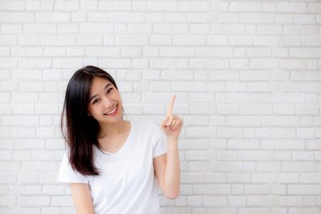 Portret pięknej młodej azjatyckiej kobiety szczęścia stałego palcem wskazującym coś na szarym tle tekstury cementu ściana cegła grunge, bizneswoman jest uśmiechnięta na betonie, koncepcja ludzi biznesu.