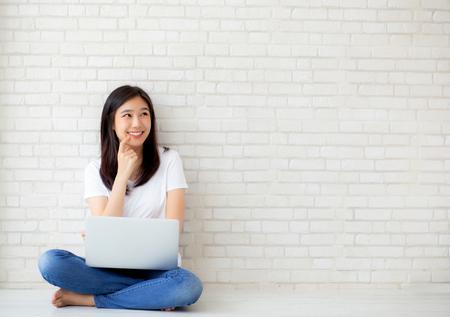 Schön von der jungen asiatischen Frau des Porträts, die Online-Laptop arbeitet und denkt, auf Bodenziegelzementhintergrund, freiberufliches Mädchen unter Verwendung des Notizbuchcomputers, Geschäfts- und Lebensstilkonzepts sitzend zu sitzen. Standard-Bild