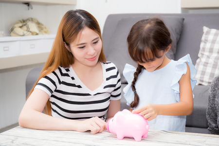 Asian mother and daughter putting coin in piggy bank, mom and kid with deposit account family together saving money for future, finance account concept. 免版税图像