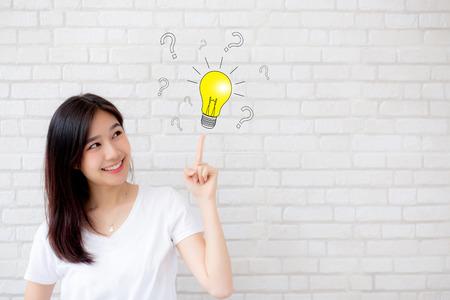 Mujer asiática pensando con dibujo de signo de interrogación para la decisión y tener una idea y señalar con el dedo la luz sobre fondo de ladrillo de pared de grunge de textura de cemento gris, genio de inspiración para el concepto de éxito.