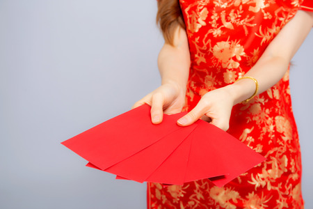 Closeup asian woman cheongsam dress holding red envelope on white background, girl celebrate with exciting, happy Chinese New Year, holiday concept.