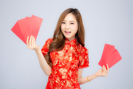 Beautiful portrait young asian woman cheongsam dress smiling holding red envelope on white background, girl celebrate with exciting, happy Chinese New Year, holiday concept.