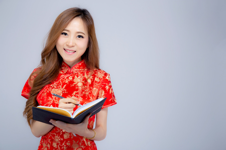 Beautiful portrait young asian woman wear red cheongsam writing notebook isolated on white background, girl study and leaning, Chinese New Year holiday concept.