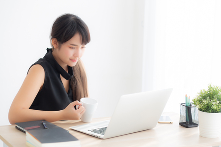 Beautiful young freelance asian woman smiling working and on laptop computer at desk office with professional, girl using notebook and drink coffee, business and lifestyle concept. Stock Photo