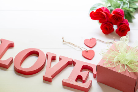 Present gift with red rose flower and gift box with bow ribbon and wood heart shape on wooden table, 14 February of love day with romantic, valentine holiday concept. Stock Photo