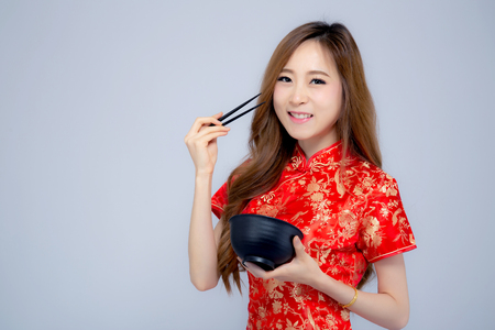 Beautiful portrait young asian woman wear red cheongsam holding chopsticks and bowl isolated on white background, Chinese New Year holiday concept.