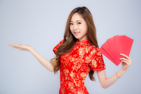 Beautiful portrait asian woman cheongsam dress holding red envelope and presenting something copy space on white background, happy Chinese New Year, holiday concept.