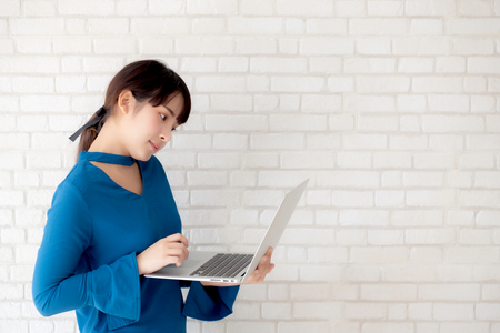 Beautiful portrait asian young woman smile using laptop standing at workplace on cement concrete background, girl happy with computer internet online, lifestyle and freelance business concept.