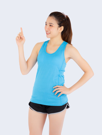 Beautiful portrait young asian woman in sport clothing with satisfied and confident isolated on white background, girl asia have wellness finger point something, exercise for fit with health concept.