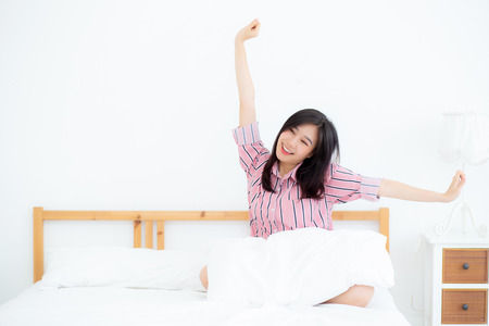Beautiful of portrait young asian woman stretch and relax in bed after wake up morning at bedroom, new day and resting for wellness, lifestyle concept.