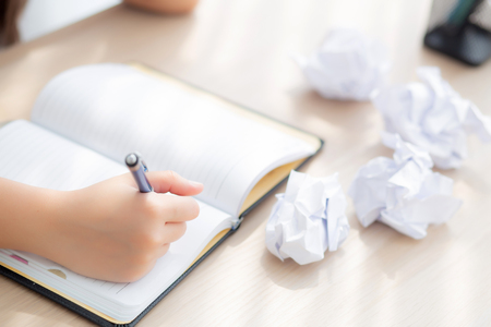 Closeup asian woman tired and stressed with writing overworked at desk, girl with worried not idea with notebook and crumpled paper at office, freelance and business concept. 版權商用圖片
