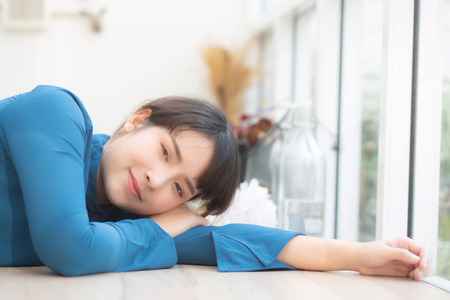 Beautiful portrait young asian woman smiling sitting lying at cafe, model girl happy with relax and resting looking camera, lifestyle concept.