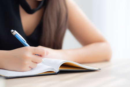 Closeup hand asian woman sitting study and learning writing notebook and diary on table in living room at home, girl homework, business writer woman working on table, education concept. Stock Photo
