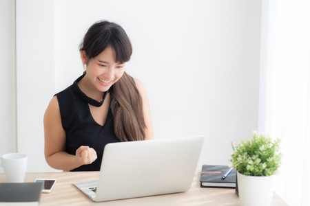 Beautiful portrait asian young woman smile working online laptop computer with happy satisfied sitting on desk office, girl using notebook with excited and glad, business and success concept.