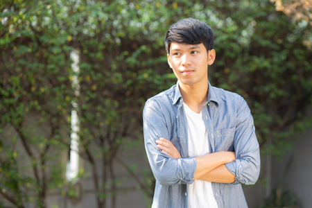 Beautiful portrait young handsome asian man standing and smile with sunlight at morning, male looking camera with happy, guy wear casual with cheerful, lifestyle and relax concept.