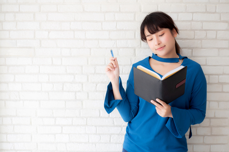 Beautiful asian woman smiling standing thinking and writing notebook on concrete cement white background at home, girl homework on book, education and lifestyle concept.