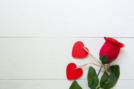 Present gift with red rose flower and heart shape on wooden table, 14 February of love day with romantic copy space, valentine holiday concept, top view.