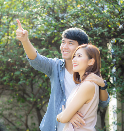 Beautiful portrait couple looking each others eyes and smiling with happy, young asian man and woman relation pointing something, husband and wife feeling and emotion, lovers and lifestyle concept.