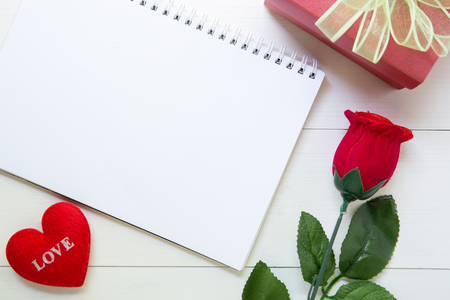 Present gift with red rose flower and notebook and heart shape with copy space on wooden table, 14 February of love day with romantic, valentine holiday concept.