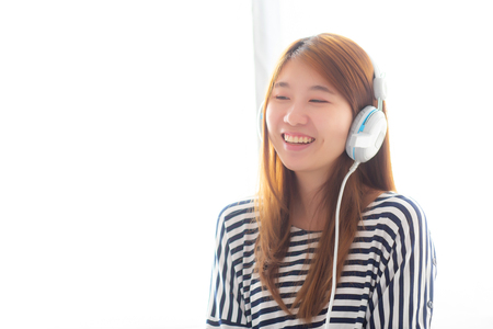 Beautiful asian young woman enjoy and fun listen music with headphone sitting in bedroom, girl relax with earphone, leisure and technology concept.