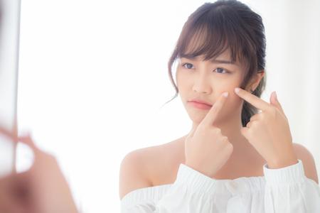 Portrait belle jeune femme asiatique regardant le miroir est une acné, traitement zit, problème de fille beau visage, beauté parfaite avec bien-être dans la chambre à la maison avec soins de la peau et concept de soins de santé.