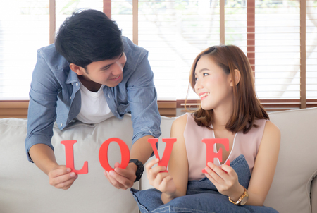 Beautiful portrait young asian couple sitting on sofa holding word love together in living room, family husband and wife smiling with happy, man and woman lover wearing casual with relax, lifestyle co 写真素材