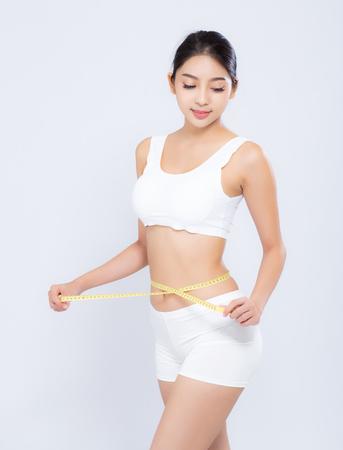 mooi portret Aziatische vrouw dieet en slank met het meten van taille voor gewicht geïsoleerd op een witte achtergrond, meisje heeft cellulitis en calorieën verlies met meetlint, gezondheid en wellness concept. Stockfoto