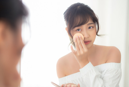 Portrait beautiful young asian woman applying powder puff at cheek makeup of cosmetic looking mirror, beauty of girl with skin face smile in the bedroom, health and wellness concept.