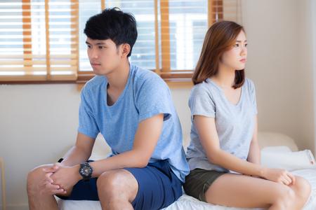 Relazione di giovane coppia asiatica che ha problemi a letto nella camera da letto a casa, famiglia che litiga con infelice, uomo e donna con problemi, fallimento e stress insieme.