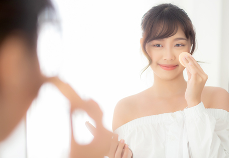 Portrait beautiful young asian woman applying powder puff at cheek makeup of cosmetic looking mirror, beauty of girl with skin face smile in the bedroom, health and wellness concept. Stock Photo - 121121055