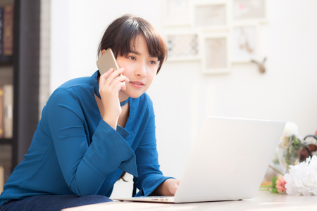 Beautiful asian young businesswoman excited and glad of success work with laptop, girl taking mobile smart phone and working coffee shop, career freelance business concept.