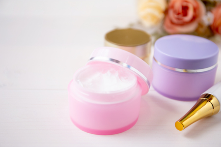 cosmetic and skin care product and flower on white wood table, beauty with treatment cream and moisturizing on wooden desk, health and wellness concept.