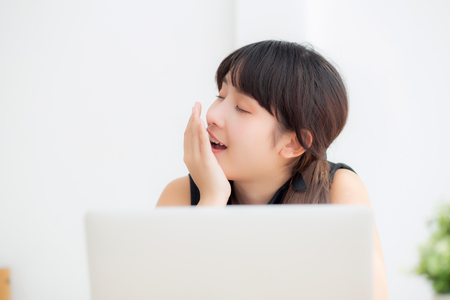 beautiful young freelance asian woman working bored and tired on laptop computer at the office, girl lazy sleepy and yawning on notebook, female secretary with exhausted, business concept. Stock Photo