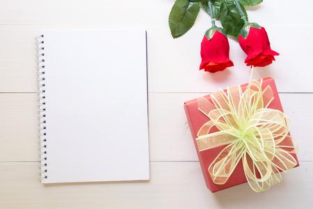 Präsentieren Sie rote Rosenblüte und Notizbuch und Geschenkbox mit Kopienraum auf Holztisch, 14. Februar des Liebestages mit romantischem Valentinstagskonzept.