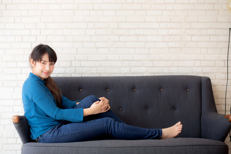 Beautiful portrait young asian woman sitting and smiling happy and looking at camera on sofa with casual at living room, girl cheerful and relax on couch at home, lifestyle concept.