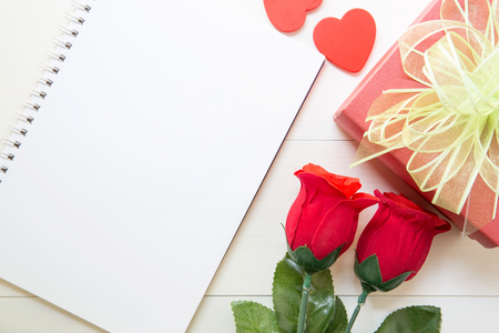 Present red rose flower and notebook and gift box and heart shape with copy space on wooden table, 14 February of love day with romantic, valentine holiday concept.